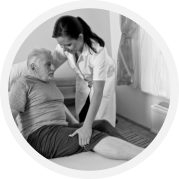 A caregiver assisting an elderly in laying down