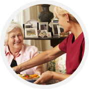 A caregiver giving meal to an elderly