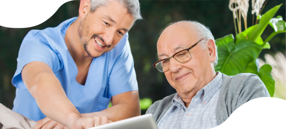 An elderly holding a tablet device while listening to a caregiver